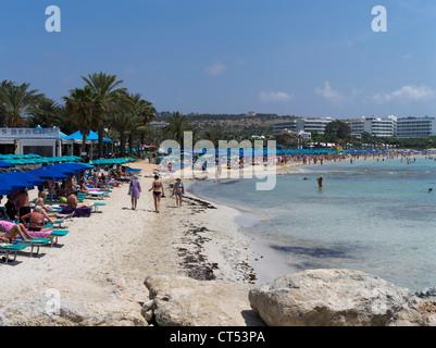 dh Liminaki beach AYIA NAPA CYPRUS Blue umbrellas lining white sand beach tourist bathers and hotels - Stock Photo