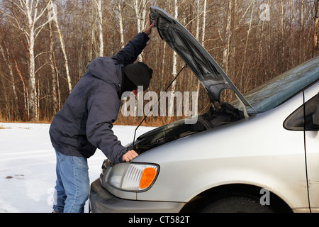 Man looking under the hood of a vehicle in winter. - Stock Photo