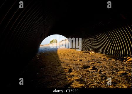 Setting sun as seen through tunnel running under road, Twentynine Palms, California, USA. - Stock Photo