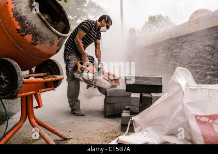A workman using an angle grinder power tool to cut a concrete block, UK - Stock Photo
