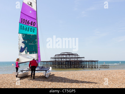 Man and woman preparing a catamaran for sail off the beach at Brighton and Hove in front of the remains of the West - Stock Photo