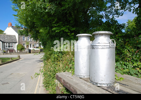 Milk churns by the roadside in the village of Crantock, Cornwall, UK - Stock Photo