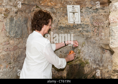 Tourist filling bottle, fountain of sacred water, House of the Virgin Mary, Meryemana, near Ephesus and Selcuk, - Stock Photo