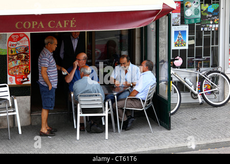 Local men playing cards outside typical street cafe , Viana do Castelo , northern Portugal - Stock Photo