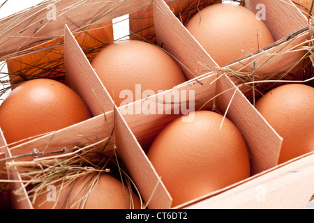 Eggs with a straw in a wooden basket - Stock Photo