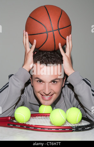 Portrait of a cheerful sportsman with basketball, tennis ball and racket - Stock Photo