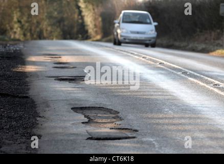 Potholes after winter weather on major roads cause damage to cars - Stock Photo