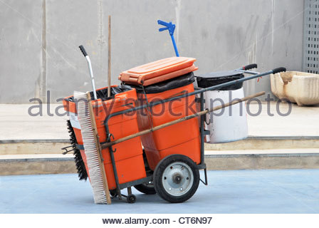 Street cleaner tools in an orange cart. Street cleaning service - Stock Photo