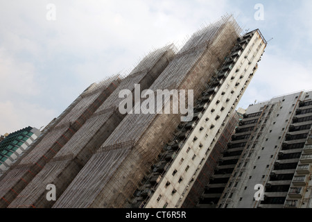 It's a photo of a tower building under construction in Hong Kong, China. We can see the bamboo scaffoldings against - Stock Photo