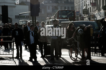 Pedestrians waiting to cross a busy road in the centre of the city of London, England. - Stock Photo
