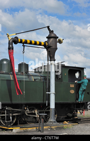 Engine driver filling boiler of steam train from water crane at the depot of Trois Vallées at Mariembourg, Belgium - Stock Photo
