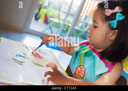 Two year old playing with paints. - Stock Photo
