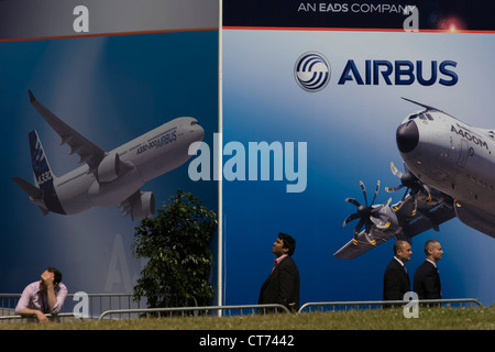 Delegates walk past a billboard of A380 airliner and military A400M transporter outside an EADS chalet at the Farnborough - Stock Photo
