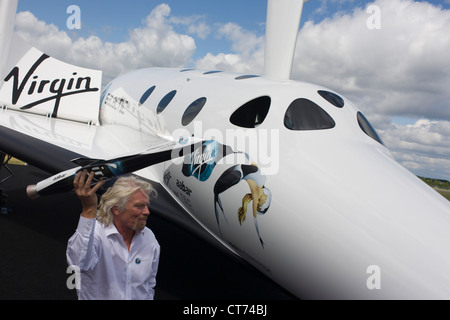 Alongside his SpaceShipTwo vehicle, Richard Branson holds model of satellite LauncherOne after Virgin Galactic space - Stock Photo