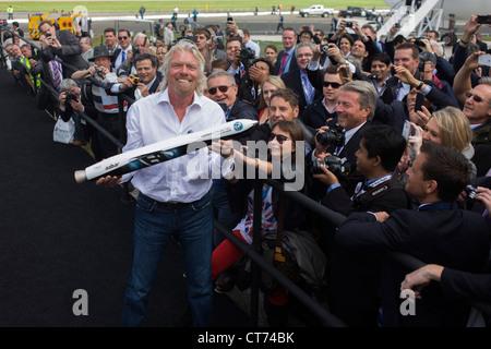 Richard Branson shows spectators a model of satellite LauncherOne after Virgin Galactic space tourism presentation - Stock Photo