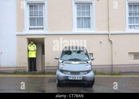 A badly parked car watched over by a policeman in Falmouth, Cornwall - Stock Photo