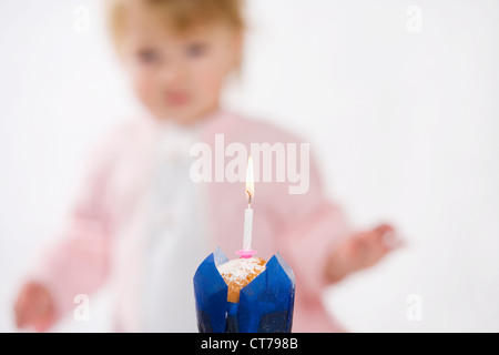 candle burning on muffin to celebrate baby´s first anniversary - Stock Photo
