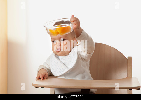 portrait of baby in high chair holding bowl with fruit - Stock Photo