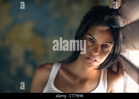 Domestic violence, portrait of abused and hurt young woman crying at home - Stock Photo