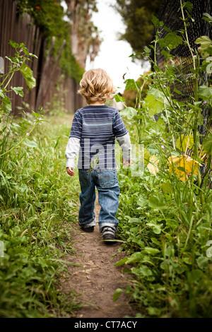 Boy walking on dirt track rear view - Stock Photo