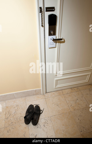 Pair of shoes by hotel room door - Stock Photo