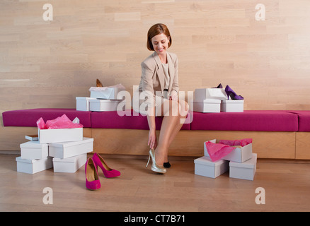 Woman trying on shoes in shoe shop - Stock Photo