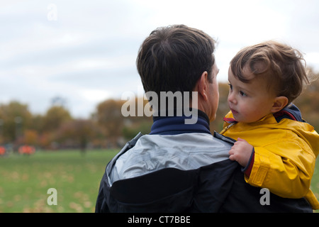 Father holding young son in park - Stock Photo