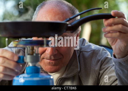 Senior man cooking on camping stove - Stock Photo