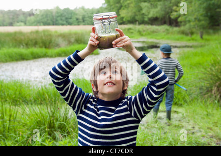 Boy looking at tadpoles in jar - Stock Photo