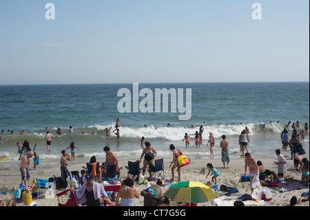 Beachgoers escape the heat wave at Rockaway Beach in the Queens borough of New York - Stock Photo