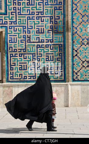 Muslim woman wearing traditional black hijab walking with her kid in Qazvin, Iran - Stock Photo
