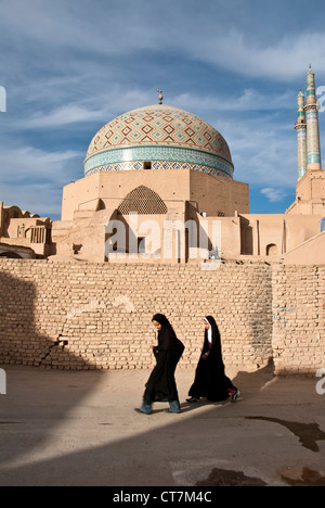 Children wearing Hijab walking in front of the Jameh Mosque of Yazd, Iran - Stock Photo