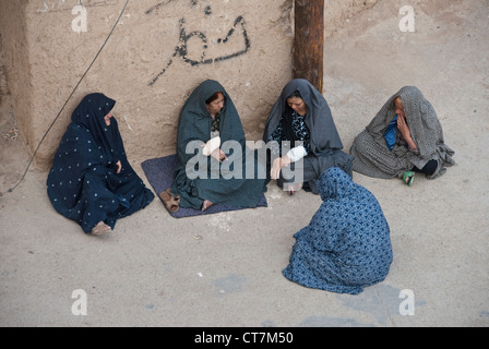 Muslim women sitting and talking on the street, Yazd, Iran - Stock Photo