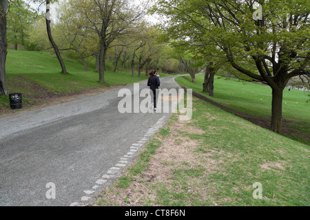A woman jogging along a cinder path in Parc Jeanne-Mance in spring Montreal, Quebec, Canada - Stock Photo