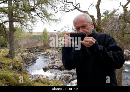 Man taking a photograph with a iphone - Stock Photo