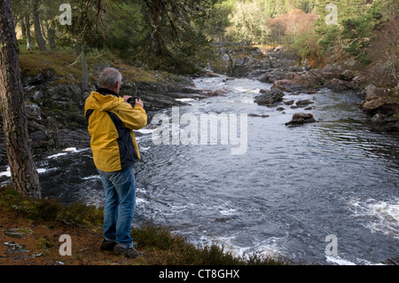 Man taking a photograph of a river in Scotland - Stock Photo