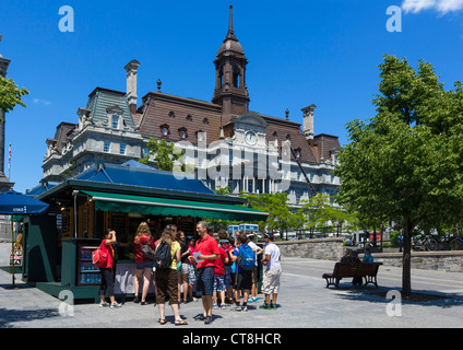 Tourists at a refreshment kiosk on Place Jacques Cartier with City Hall (Hotel de Ville) behind, Vieux Montreal, - Stock Photo