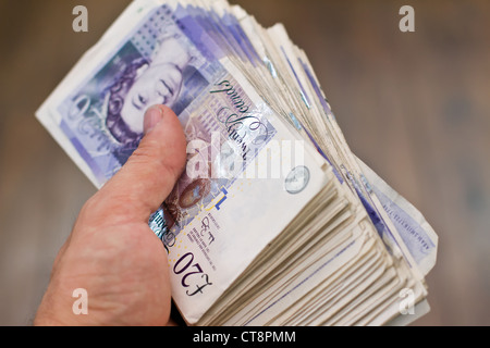 a large bundle of british twenty pound notes in the hand - Stock Photo