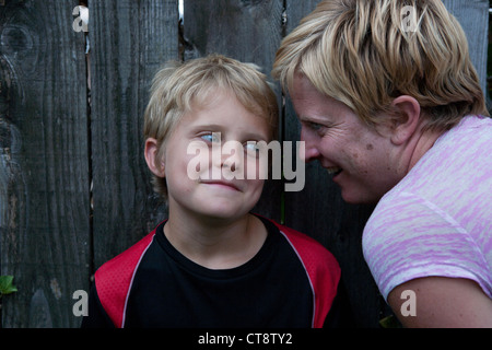 Mom whispering something in her son's ear and boy smiling. - Stock Photo
