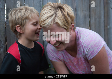 Ten year old boy telling his mother a story and mom laughing outloud. - Stock Photo