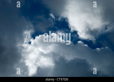 stratus clouds drifting across the sky on a bright day - Stock Photo