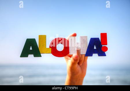 Female's hand holding colorful word 'Aloha' against blue background - Stock Photo
