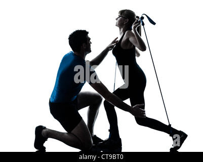 caucasian aerobics instructor  with mature woman exercising gymstick fitness workout in silhouette studio isolated - Stock Photo