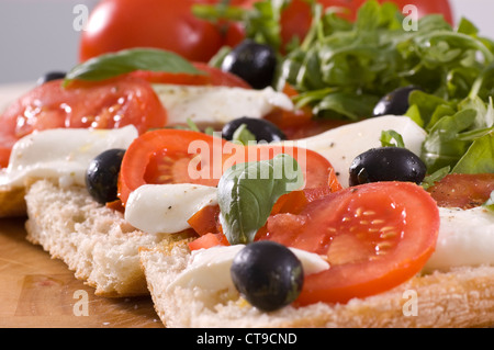 ciabatta with tomato, olives, mozzarella, basil and rocket, drizzled with olive oil - Stock Photo