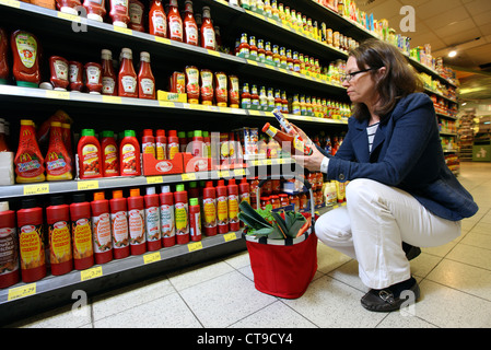 Woman is shopping in a large supermarket.  Walking between racks, filled with different food products. - Stock Photo