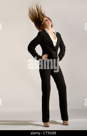 Fashionable woman is wearing a classic black pantsuit and flipping her long blond hair. - Stock Photo