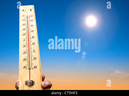 hand holding thermometer and heat weather - Stock Photo