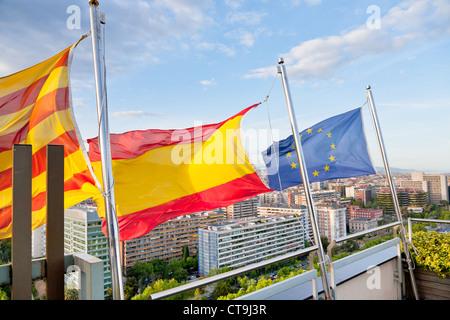 Catalan, Spanish, EU flags under Barcelona city - Stock Photo