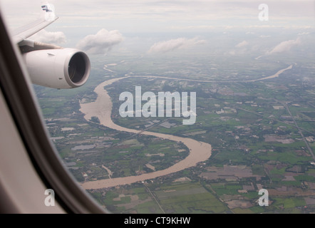 Flying over local countryside on approach to Suvarnabhumi International Airport in Bangkok, Thailand - Stock Photo