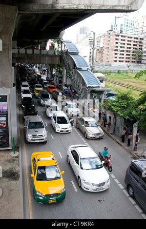 Heavy traffic on the Thanon Sukhumvit road below Nana Skytrain station in Bangkok, Thailand - Stock Photo